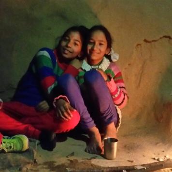 Kanika (höger) och hennes vän Sonakshi vid elden