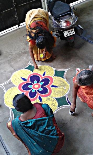 När vi kommer till kontoret på morgonen är kollegorna Meenakshi, Rani och Andal i full gång med att göra kolams.