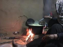 Dadi Asha rör runt i stora grytan med kheer.